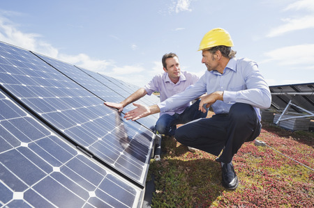 cowering: Germany,Munich,Man Discussing With Engineer In Solar Plant LANG_EVOIMAGES
