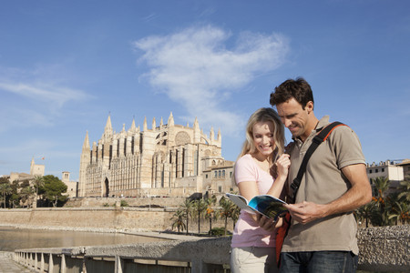 waist down: Spain,Mallorca,Palma,Couple Looking In Guide Book With St Maria Cathedral In Background,Smiling LANG_EVOIMAGES