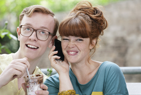 Germany,Berlin,Close Up Of Young Couple Listening To Cell Phone,Smiling LANG_EVOIMAGES