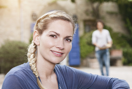Italy,Tuscany,Magliano,Close Up Of Young Woman And Man In Background,Smiling LANG_EVOIMAGES