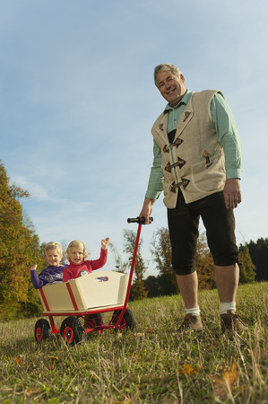 pushcart: Germany,Bavaria,Grandfather Pulling Granddaughters Sitting In Wagon