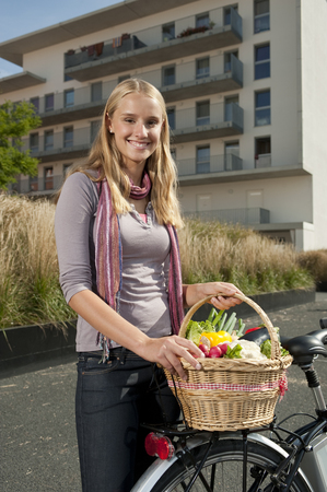 scarves: Germany,Bavaria,Teenage Girl Standing By Bicycle Holding Basket,Smiling,Portrait LANG_EVOIMAGES