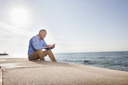 Spain,Mallorca,Senior Man Using Mobile Phone LANG_EVOIMAGES