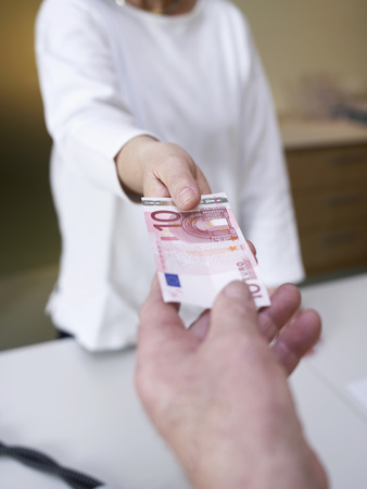 Germany,Hamburg,Woman Receiving Cash From Senior Man,Smiling
