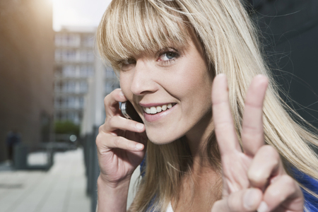 Germany,Cologne,Young Woman Using Cell Phone,Smiling,Portrait