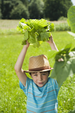 Germany,Bavaria,Boy In Garden Holding Vegetables,Smiling,Portrait