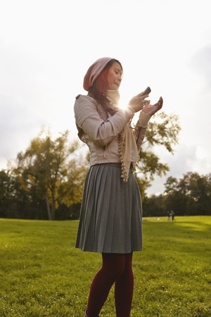 Germany,Cologne,Young Woman With Cell Phone In Park