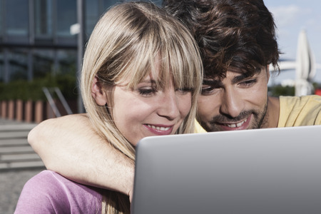 Germany,Cologne,Young Couple Using Laptop,Smiling LANG_EVOIMAGES