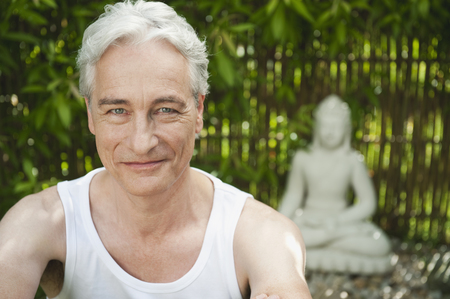 spiritual beings: Germany,Bavaria,Mature Man Smiling With Buddha Statue In Background