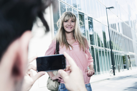hands free phone: Germany,Cologne,Young Man Capturing Photo Of Woman,Smiling