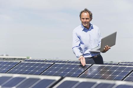 Germany,Munich,Mature Man With Laptop In Solar Plant,Portrait LANG_EVOIMAGES