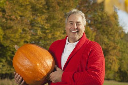 Germany,Bavaria,Mature Man Holding Pumpkin,Smiling,Portrait