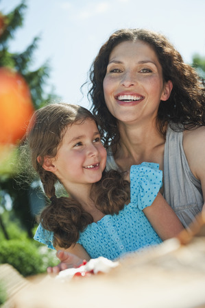 Germany,Bavaria,Mother And Daughter At Coffee Table In Garden,Smiling