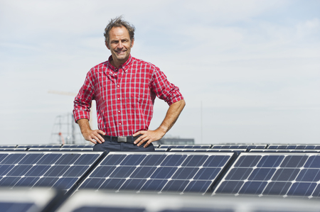 Germany,Munich,Mature Man Standing In Solar Plant,Smiling,Portrait LANG_EVOIMAGES