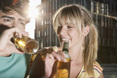 Germany,Cologne,Young Couple Drinking Beer Bottle,Smiling