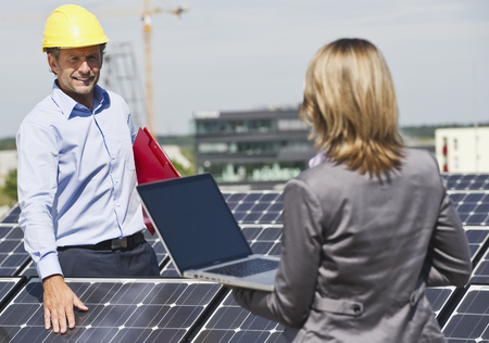 Germany,Munich,Engineers With Laptop And Discussing In Solar Plant