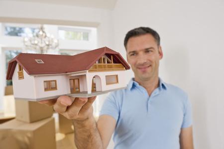 Germany,Bavaria,Grobenzell,Mature Man Holding Model House Near Cardboard Box,Smiling