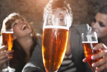 spritz: Germany,Berlin,Close Up Of Champagne Glass In Front Of Friends Having Party,Smiling