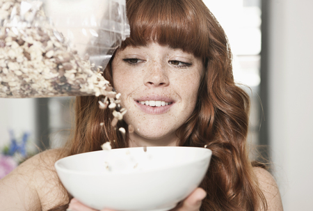 Germany,Berlin,Close Up Of Young Woman Preparing Cereals,Smiling LANG_EVOIMAGES