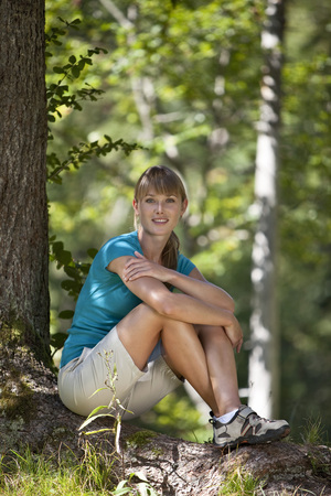 Germany,Upper Bavaria,Young Woman Resting Under Tree,Smiling,Portrait