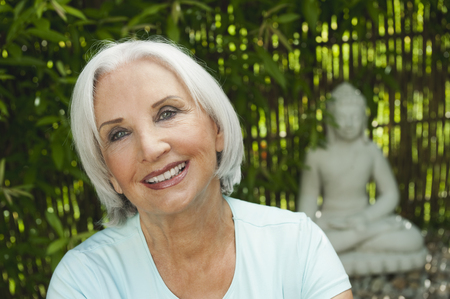 spiritual beings: Germany,Bavaria,Senior Woman Smiling With Buddha Statue In Background