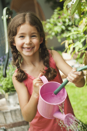 Germany,Bavaria,Girl Gardening With Watering Can,Smiling,Portrait LANG_EVOIMAGES