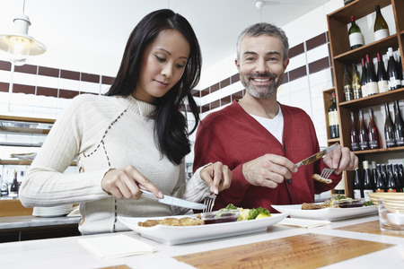Germany,Cologne,Couple Eating Food In Kitchen,Smiling LANG_EVOIMAGES