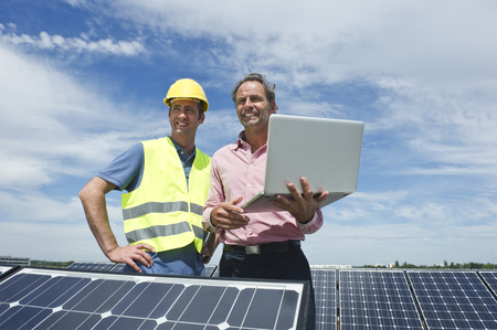 Germany,Munich,Engineers With Laptop In Solar Plant LANG_EVOIMAGES