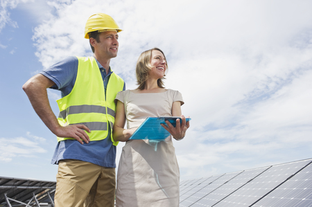 Germany,Munich,Engineers Standing In Solar Plant With Clip Boad