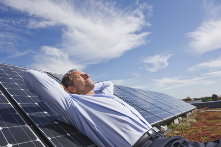 Germany,Munich,Mature Man Resting On Panel In Solar Plant,Smiling LANG_EVOIMAGES