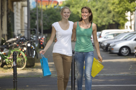 Germany,North Rhine Westphalia,Cologne,Young Women With Shopping Bags On Street,Smiling