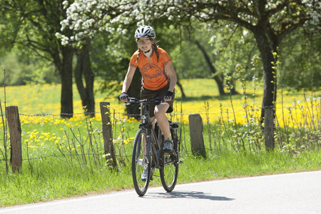 Germany,Bavaria,Young Woman Riding Bicycle LANG_EVOIMAGES