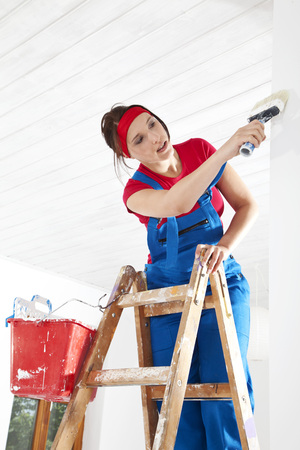 dungarees: Germany,Bavaria,Young Woman Standing On Step Ladder And Painting LANG_EVOIMAGES