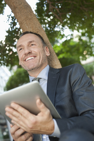 Germany,Leipzig,Businessman Sitting At Tree With Digital Tablet LANG_EVOIMAGES