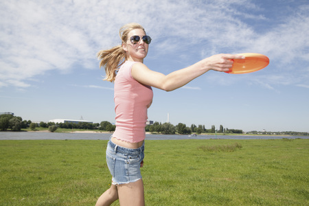 Germany,North Rhine Westphalia,Duesseldorf,Young Woman Playing With Frisbee,Smiling