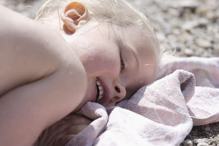Germany,Bavaria,Girl Lying On Beach Towel,Smiling,Close Up