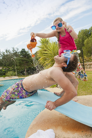 Spain,Mallorca,Couple Playing On Swimming Pool LANG_EVOIMAGES