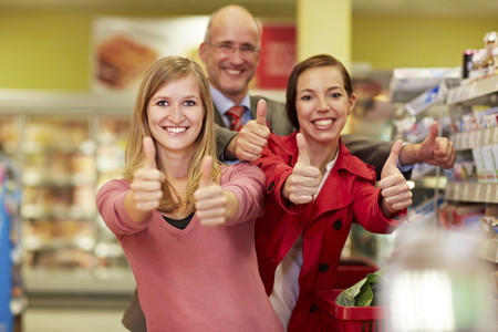 Germany,Cologne,Man And Women Showing Thumbs Up In Supermarket
