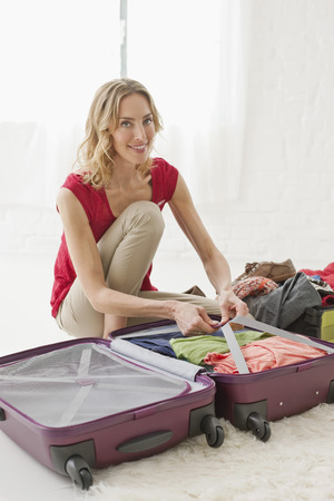 cowering: Germany,Leipzig,Mid Adult Woman Packing Suitcase,Portrait LANG_EVOIMAGES