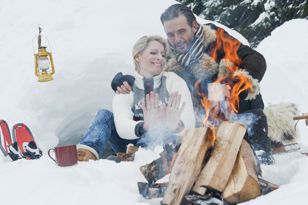 snowcovered: Austria,Salzburg County,Couple Sitting Near Fireplace LANG_EVOIMAGES