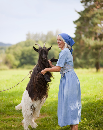 Germany,Bavaria,Mature Woman Playing With Goat On Farm