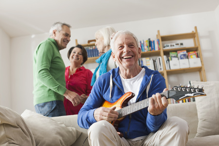 Germany,Leipzig,Senior Man Playing Electric Guitar,Man And Woman In Background