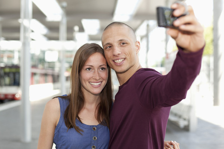 Germany,North-Rhine-Westphalia,Duesseldorf,Young Couple Photographing Self With Smart Phone LANG_EVOIMAGES