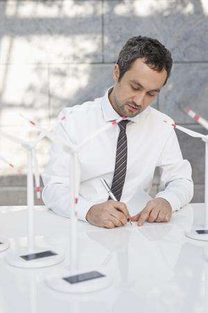 Germany,Leipzig,Businessman With Wind Power Model On Desk LANG_EVOIMAGES