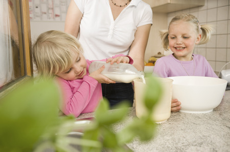 measuring cup: Mother And Daughter Pouring Milk Into Measuring Cup