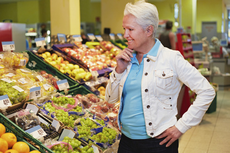 Germany,Cologne,Mature Woman Thinking In Supermarket