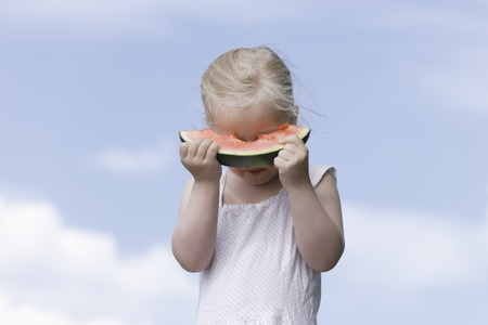 Germany,Bavaria,Girl Eating Piece Of Watermelon LANG_EVOIMAGES