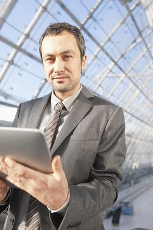 Germany,Leipzig,Businessman Using Digital Tablet On Escalator,Portrait