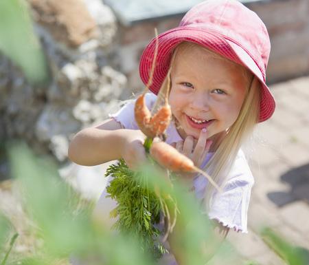 Germany,Bavaria,Girl Picking Carrots In Garden