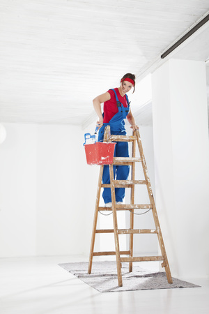 dungarees: Germany,Bavaria,Young Woman On Step Ladder And Painting